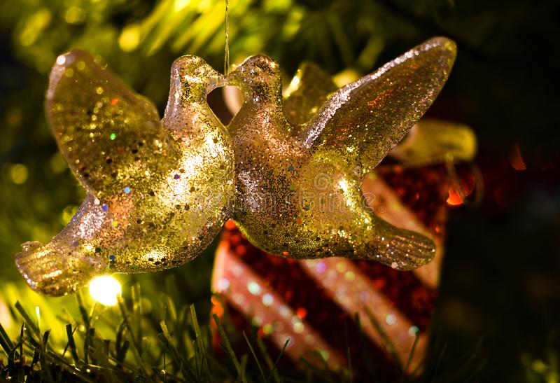 Weihnachtsdekoration von zwei Turteltauben, die in einem Baum vor einem eingewickelten Geschenk küssen stockfotografie