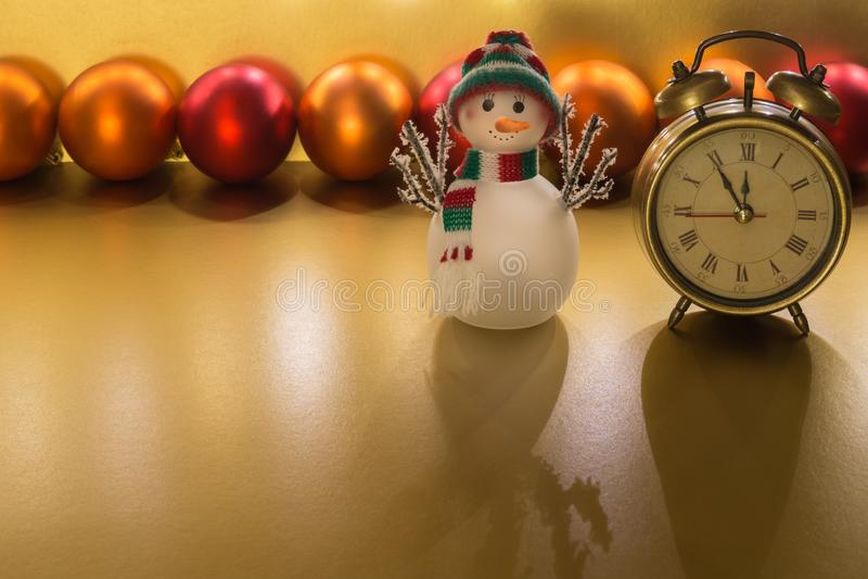 Weihnachtsdekoration - Weckerorange, Glasschneemann, orange und und roter Flitter auf goldenem Hintergrund stockfoto