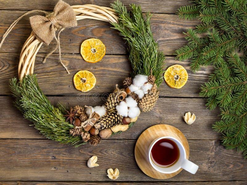Weihnachtsdekoration, Weihnachtskranz, Weihnachtsbaumaste und Tasse Tee auf Weinleseholzbeschaffenheit stockfotografie