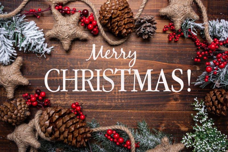 Weihnachtsdekorationen auf einem braunen hölzernen Hintergrund mit Kopienraum Kiefernkegel, Girlande, Beeren und Kiefernniederlas lizenzfreies stockfoto