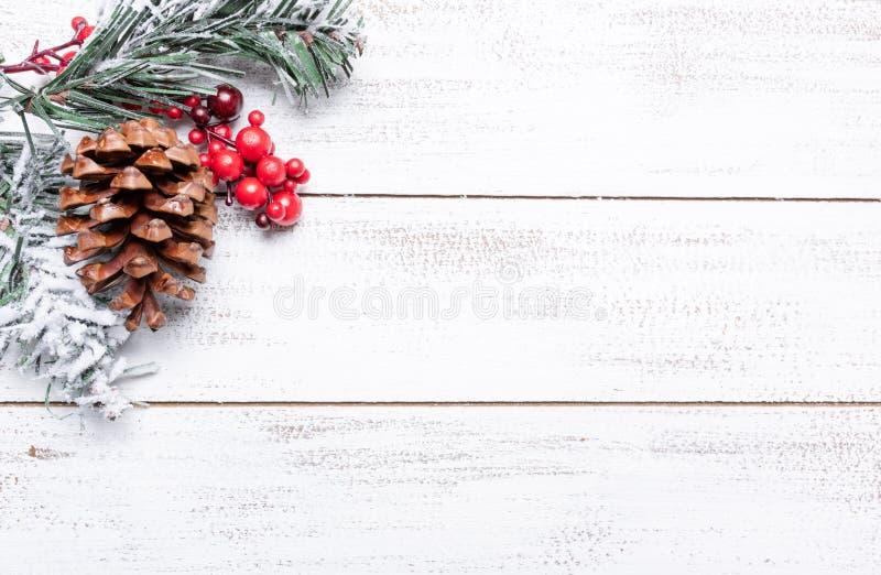 Weihnachtsdekorationen auf einem weißen hölzernen Hintergrund mit Kopienraum Kiefernkegel, Girlande, Beeren und Kiefernniederlass stockbilder