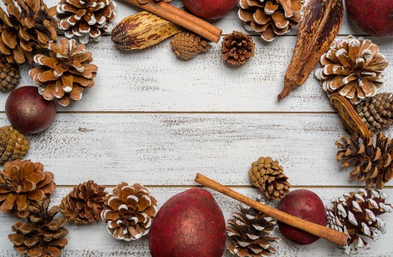 Weihnachtsdekorationen auf einem weißen hölzernen Hintergrund mit Kopienraum Kiefernkegel, Girlande, Beeren und Kiefernniederlass stockfotos