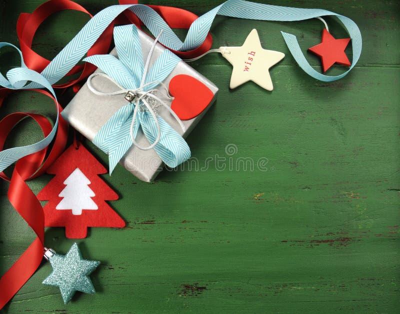 Weihnachtsdekorationen auf Weinlese grünen hölzernen Hintergrund, mit silbernem Geschenk stockfotos