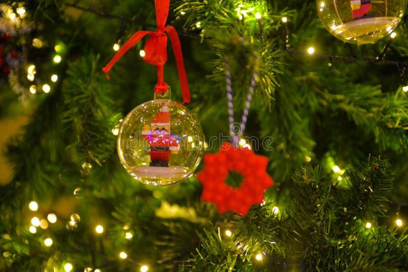 Weihnachtsdekorationen, Ball mit Lego Santa Claus, Weihnachtsbaum-Lichter, unscharfer roter Lego Ice Flake stockfoto