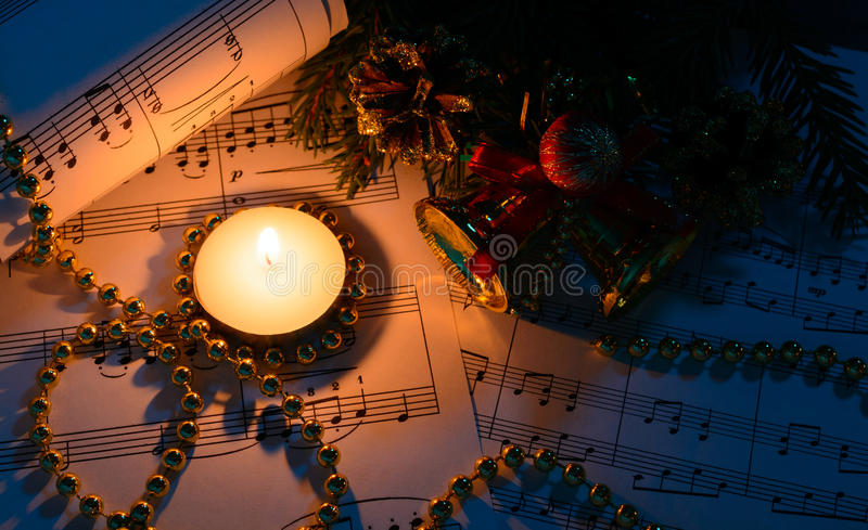 Weihnachtsdekorationen, brennende Kerze und Noten lizenzfreies stockfoto