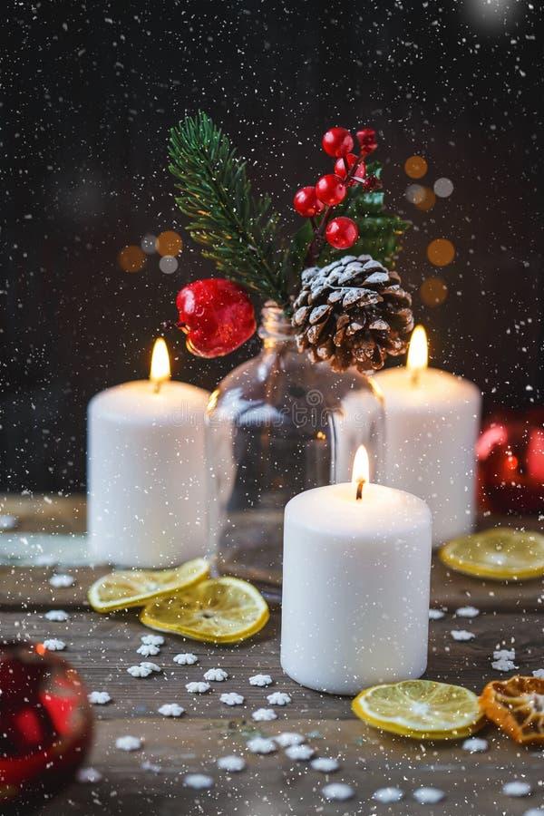 Weihnachtsdekorationen, brennende Kerzen, Süßigkeit, Schneeflocken, Zitrusfrucht, Fichte auf einem hölzernen Hintergrund Neues Ja lizenzfreie stockbilder