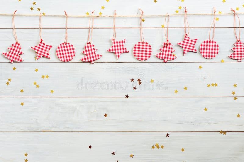 Weihnachtsdekorationen, die am hölzernen Hintergrund mit fallendem goldenem Stern hängen lizenzfreie stockbilder