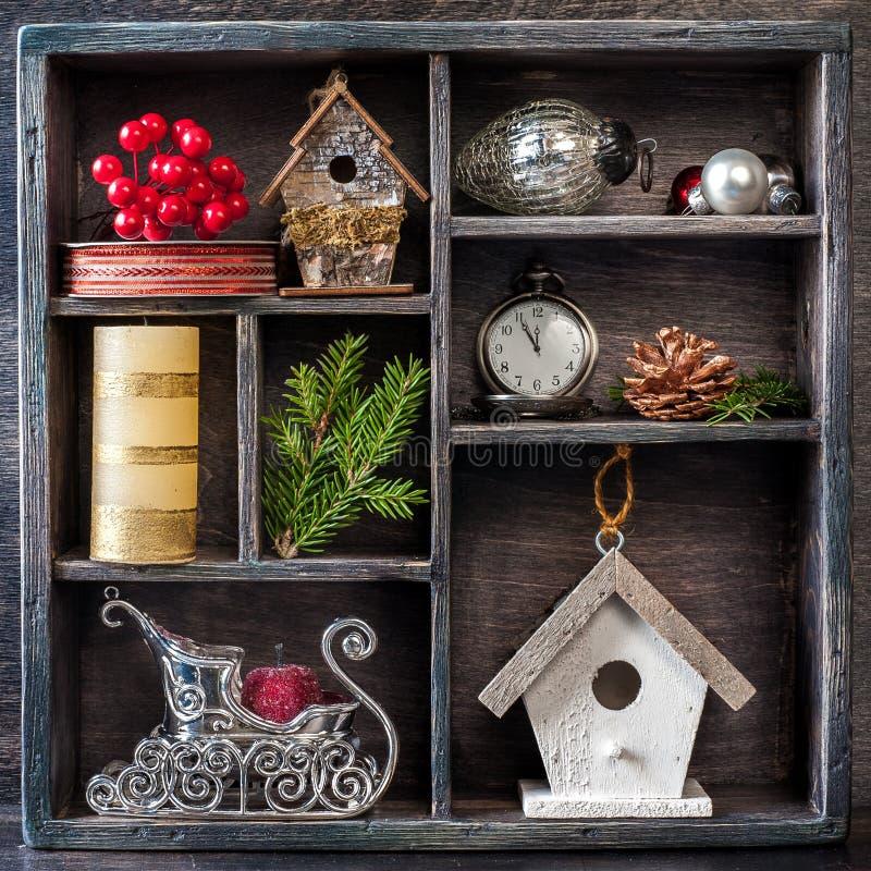 Weihnachtsdekorationen eingestellt: antike Uhren, Vogelhaus, Sankt Pferdeschlitten und Weihnachtsspielwaren in einer Weinleseholzk stockfotografie