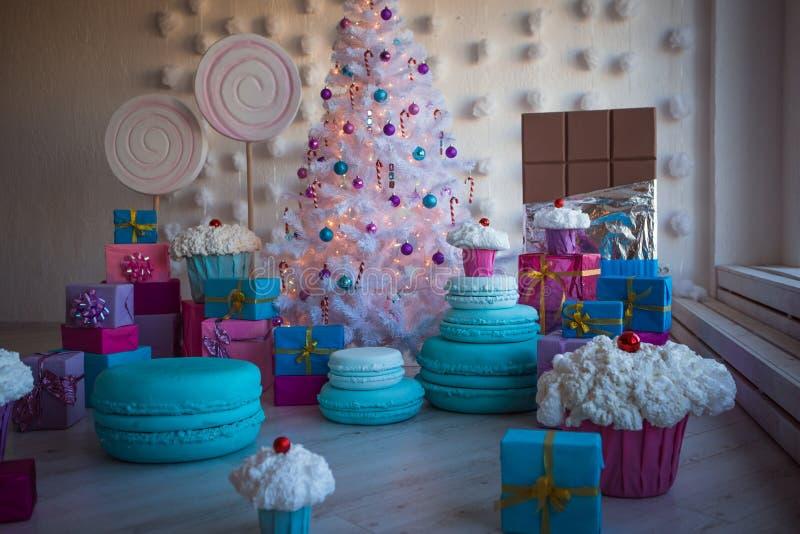 Weihnachtsdekorationen in Form von Kuchen und großer Schokolade Weihnachtsspielwaren auf einem weißen künstlichen Weihnachtsbaum stockfotos