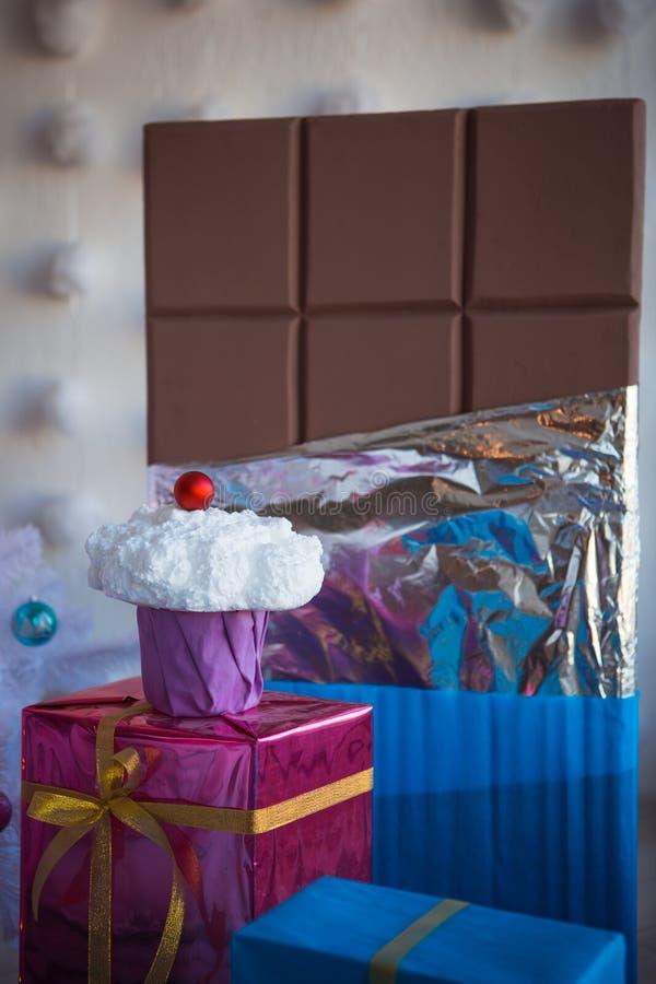 Weihnachtsdekorationen in Form von Kuchen und großer Schokolade Weihnachtsspielwaren auf einem weißen künstlichen Weihnachtsbaum stockbild
