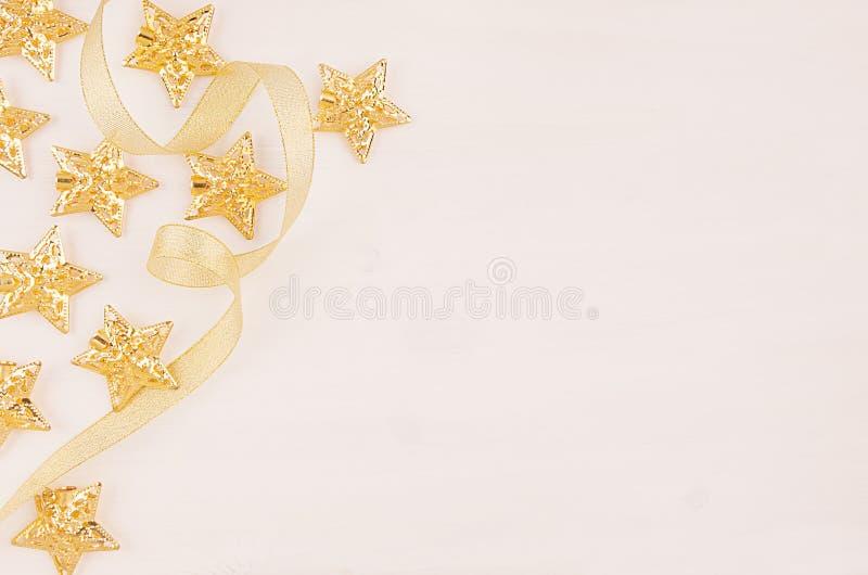 Weihnachtsdekorationen, Goldsterne kräuseln Band auf weichem weißem hölzernem Hintergrund, kopieren Raum lizenzfreie stockbilder