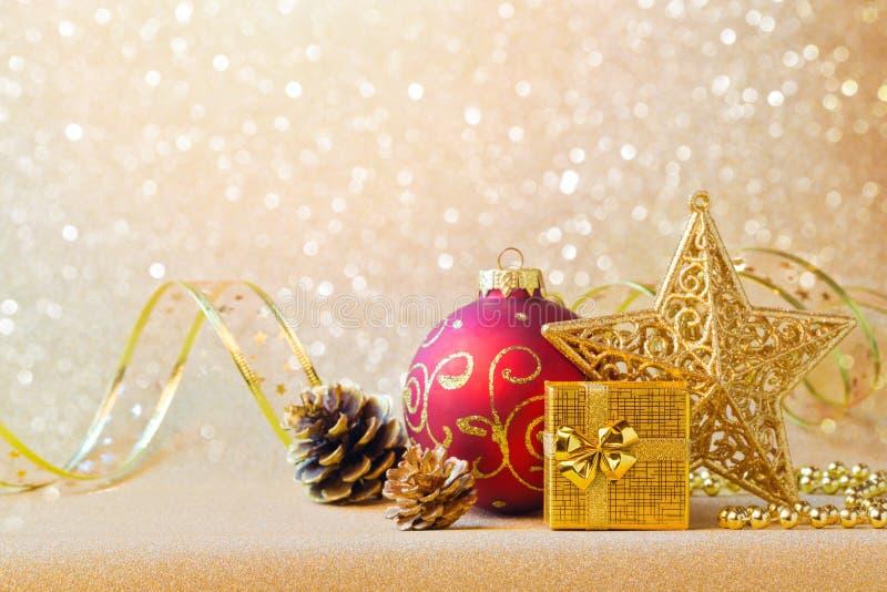 Weihnachtsdekorationen im Rot und Gold über Funkelnhintergrund stockbild