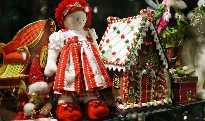 Weihnachtsdekorationen im Spielzeugshopfenster einschließlich traditionelles rotes ragdoll und Lebkuchenhaus lizenzfreie stockfotos