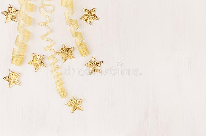 Weihnachtsdekorationen, Lockenband und Goldsterne, die auf weichen weißen hölzernen Hintergrund fallen stockfotos