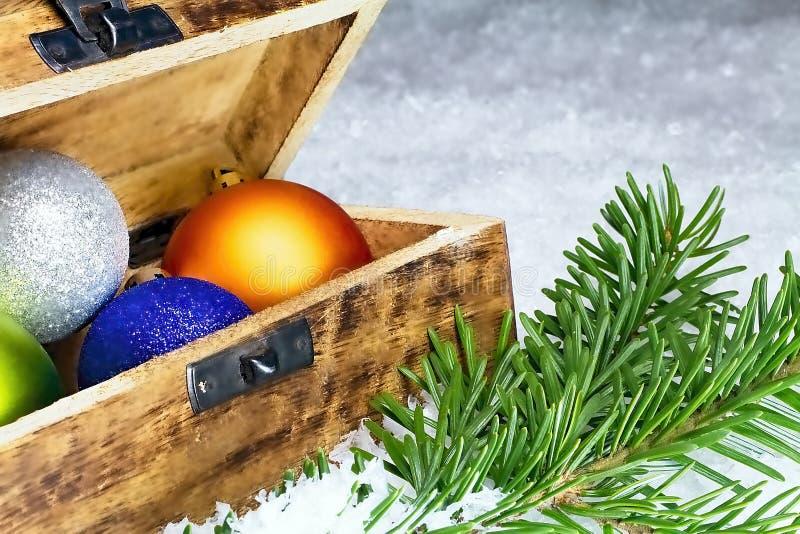 Weihnachtsdekorationen mit Weihnachtsbällen in einem Kasten und in einem Fichtenzweig Frohe Weihnachten stockfotos