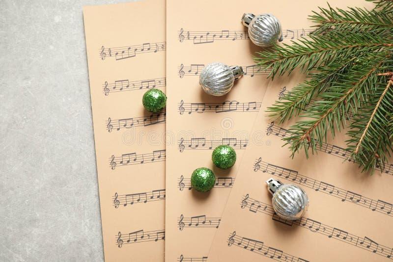 Weihnachtsdekorationen und Musikblätter auf grauen Steinen stockfotografie