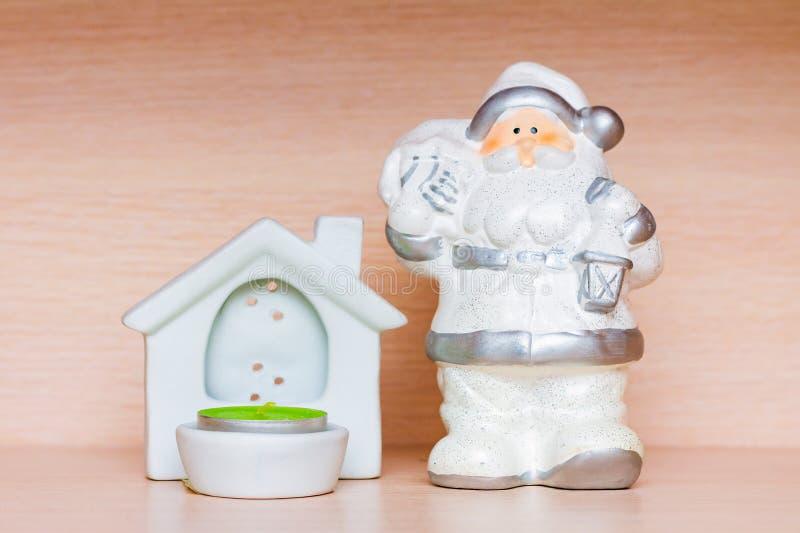 Weihnachtsdekorationen, weiße keramische Figürchen von Weihnachtsmann und Kerzenhalter mit Teekerze lizenzfreie stockbilder