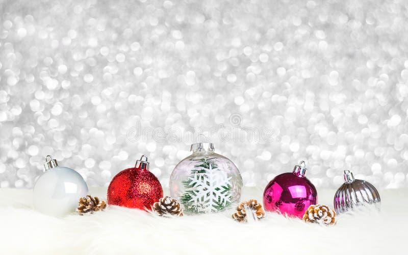 Weihnachtsdekorationsball auf weißem Pelz an silbernem bokeh Licht-BAC lizenzfreie stockfotografie