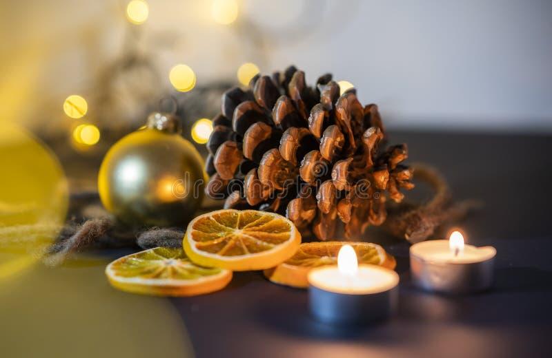 Weihnachtsdekorationsnahaufnahme eines pinecone mit candel, Weihnachtsball und Kettenlichtern auf einem undeutlichen Hintergrund stockfotografie