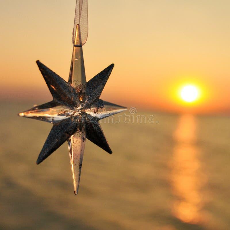 Weihnachtsdekorationsstern auf dem Hintergrund des Sonnenuntergangs auf dem Meer quadrat lizenzfreie stockbilder