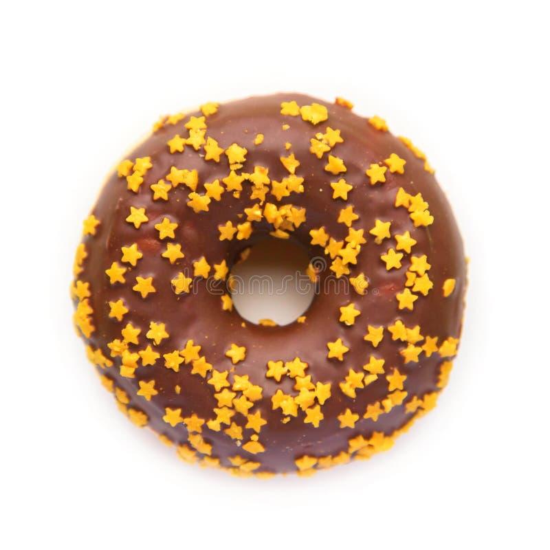Weihnachtsdonut mit Schokoladenzuckerglasur und goldenen Sternen stockbild