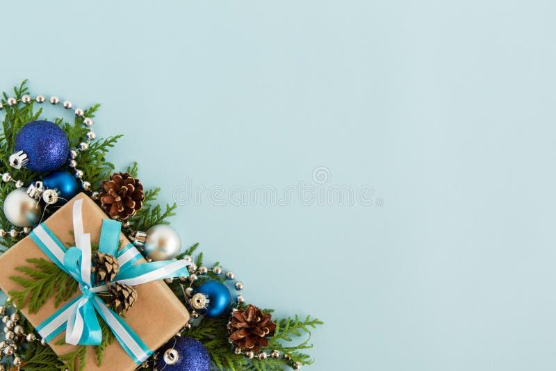 Weihnachtsebene legen Zusammensetzung von Tannenzweigen mit Geschenkbox und von Dekorationen mit Kopienraum auf den blauen Hinter stockbild