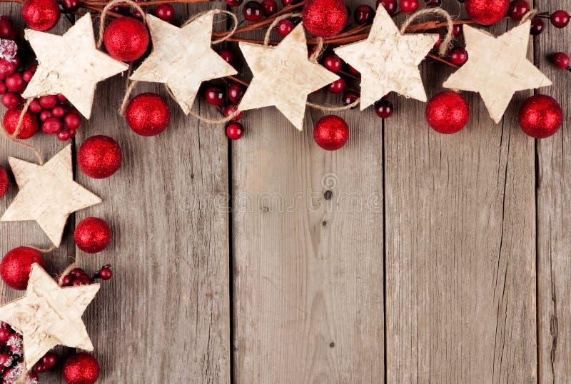 Weihnachtseckgrenze mit rustikalen hölzernen Sternverzierungen und -flitter über gealtertem Holz lizenzfreie stockbilder