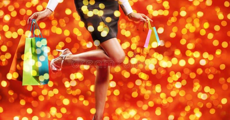 Weihnachtseinkaufen, Beinfrau mit Schuhen und Taschen auf unscharfem Br stockbild