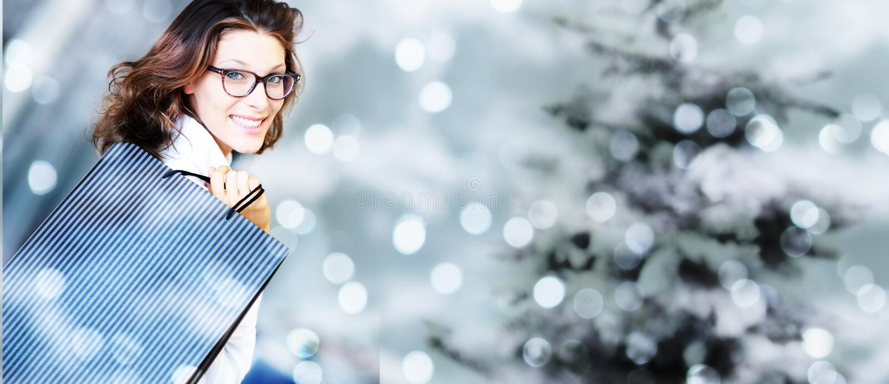 Weihnachtseinkaufen, lächelnde Frau mit Taschen auf unscharfem hellem Li lizenzfreie stockfotos