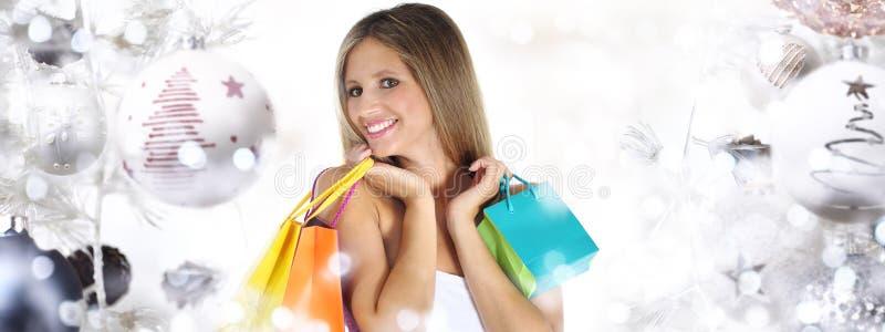 Weihnachtseinkaufen, lächelnde Frau mit Taschen auf Weihnachtsball tr lizenzfreie stockbilder