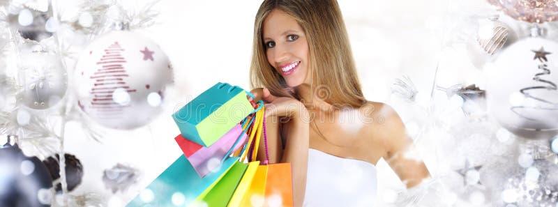 Weihnachtseinkaufen, lächelnde Frau mit Taschen auf Weihnachtsball tr stockfotos