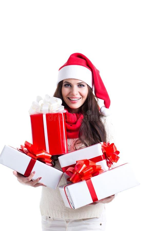 Weihnachtseinkaufenfrau, die viele Weihnachtsgeschenke in ihren Armen tragen Sankt-Hut und Winterkleidung anhält stockfotografie