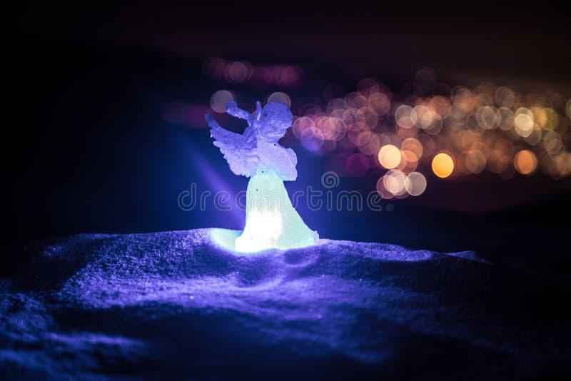 Weihnachtsengel auf Unschärfe bokeh Stadtlichtern nachts auf Hintergrund Wenig weißer Schutzengel im Schnee stockbilder