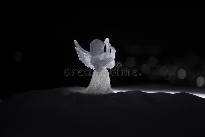 Weihnachtsengel auf Unschärfe bokeh Stadtlichtern nachts auf Hintergrund Wenig weißer Schutzengel im Schnee lizenzfreie stockfotografie