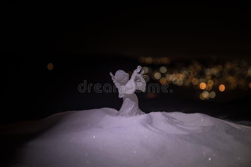 Weihnachtsengel auf Unschärfe bokeh Stadtlichtern nachts auf Hintergrund Wenig weißer Schutzengel im Schnee lizenzfreies stockbild