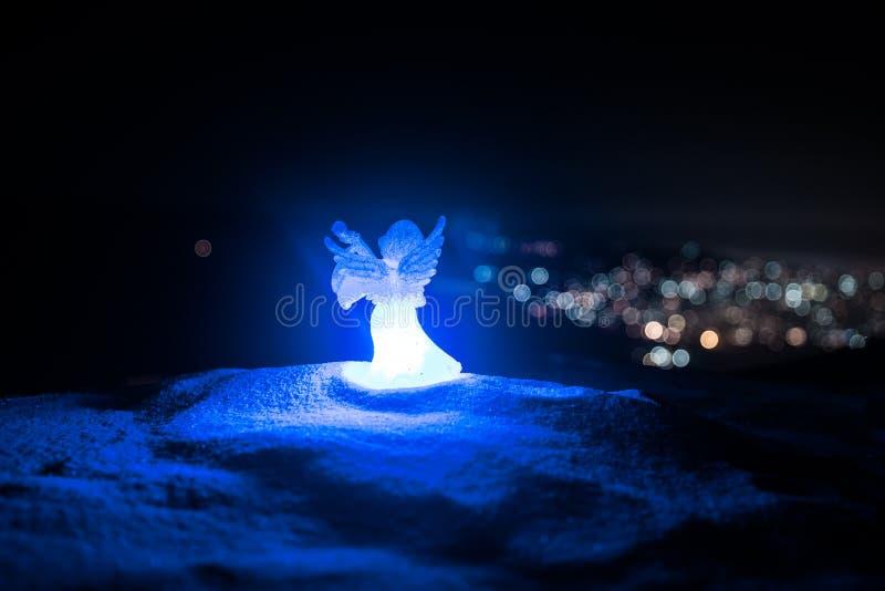 Weihnachtsengel auf Unschärfe bokeh Stadtlichtern nachts auf Hintergrund Wenig weißer Schutzengel im Schnee lizenzfreie stockfotos
