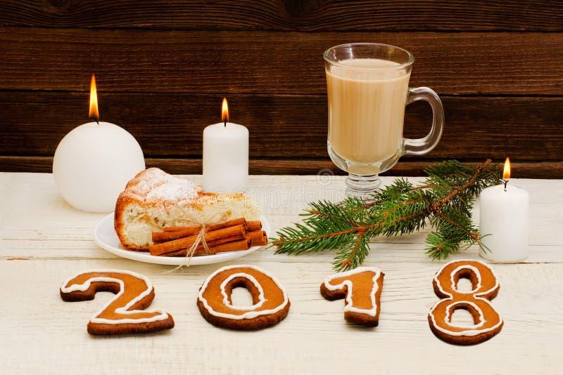Weihnachtsessen, die Zahl im Jahre 2018 des Lebkuchens, Fichtenzweig, Kerze, Cappuccino und Apfelkuchen stockbild