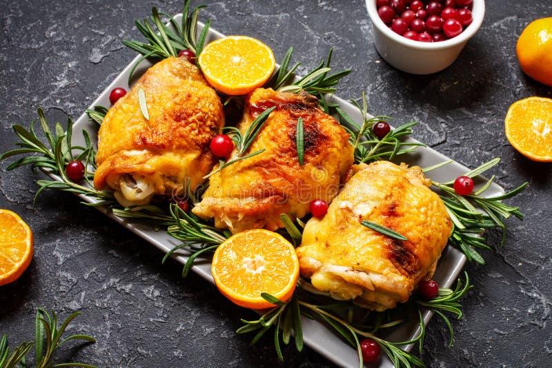 Weihnachtsessen Hühnerfleisch, gebacken mit Cranbeeren, Tangerinen und Rosemary auf SteinBacksteinhintergrund stockfotografie
