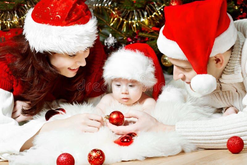 Weihnachtsfamilie in den roten Hüten, die Geschenke geben lizenzfreies stockbild