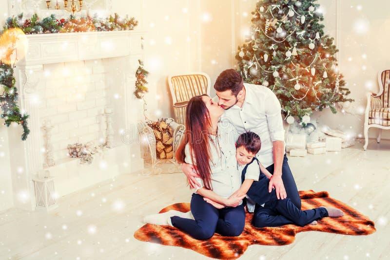 Weihnachtsfamilie, die nahe dem Weihnachtsbaum lächelt und küsst Wohnzimmer verziert durch Weihnachtsbaum und anwesende Geschenkb lizenzfreies stockfoto