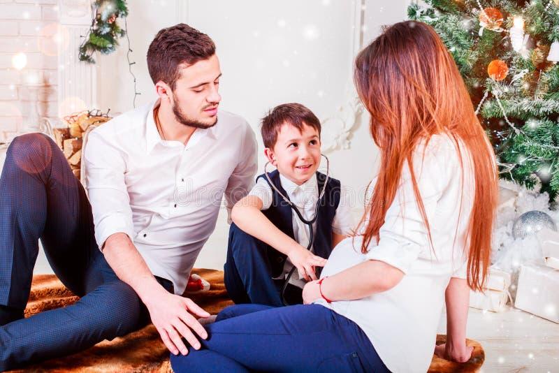 Weihnachtsfamilie, die nahe dem Weihnachtsbaum lächelt und küsst Wohnzimmer verziert durch Weihnachtsbaum und anwesende Geschenkb stockfotografie