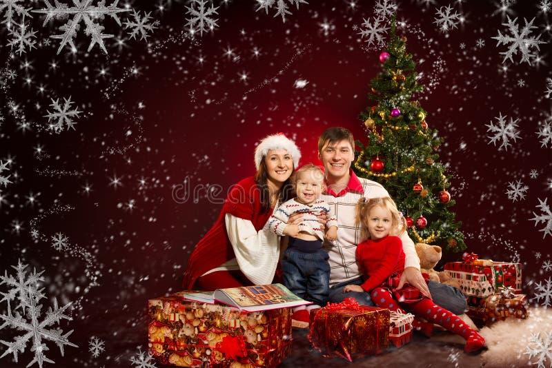 Weihnachtsfamilie, Tannenbaum mit Geschenkkästen stockfotos