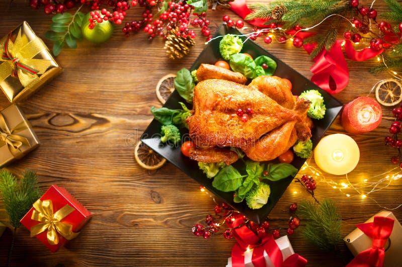 Weihnachtsfamilienabendessen Gebratenes Huhn auf der Feiertagstabelle, verziert mit Geschenkboxen, brennenden Kerzen und Girlande stockbilder