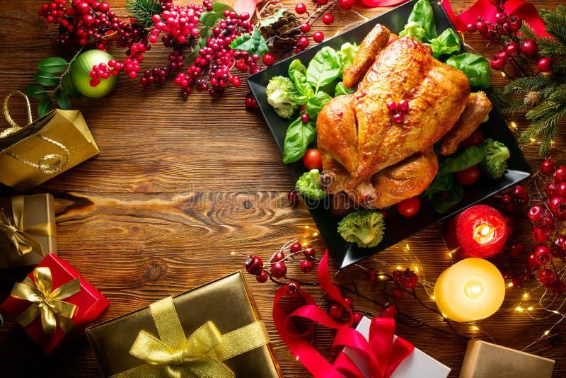 Weihnachtsfamilienabendessen Gebratenes Huhn auf der Feiertagstabelle, verziert mit Geschenkboxen, brennenden Kerzen und Girlande stockfotos