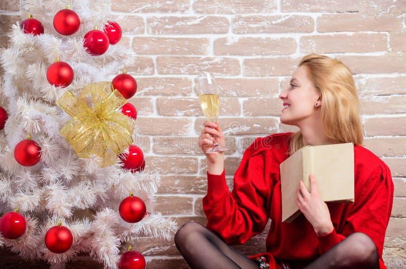 Weihnachtsfeierkonzept Viele Feiertagsverzierungen und -geschenke Noel und Freude Mädchen im roten Kleid, das mit Glas Champagner stockfotos