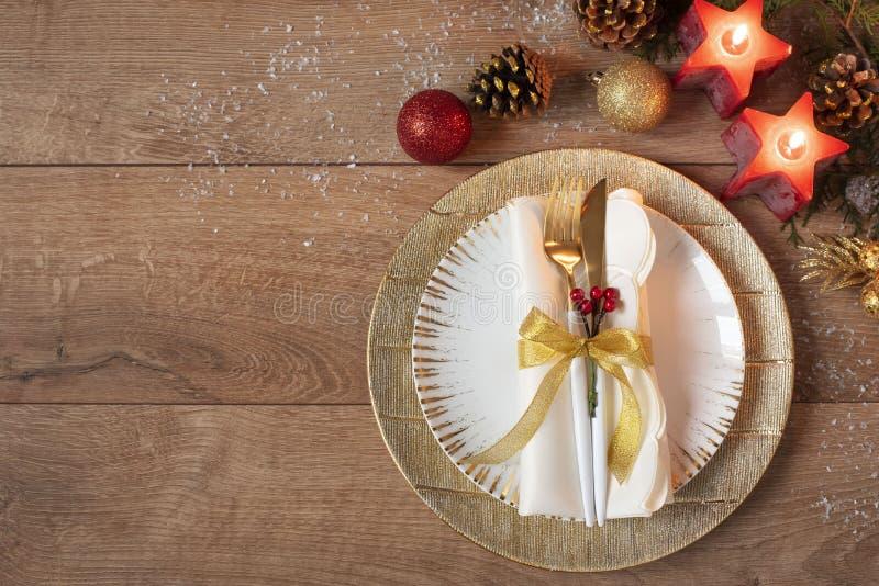 Weihnachtsfeiertags-Abendessengedeck - Platten, Serviette, Tischbesteck, Goldflitterdekorationen über Hintergrund des eichenen Ti lizenzfreie stockfotografie
