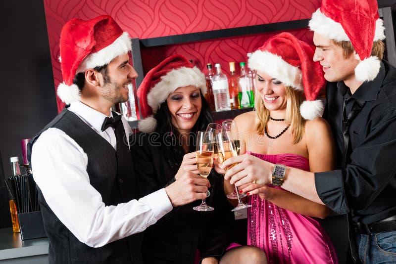 Weihnachtsfestfreunde am Stabtoastchampagner lizenzfreie stockbilder