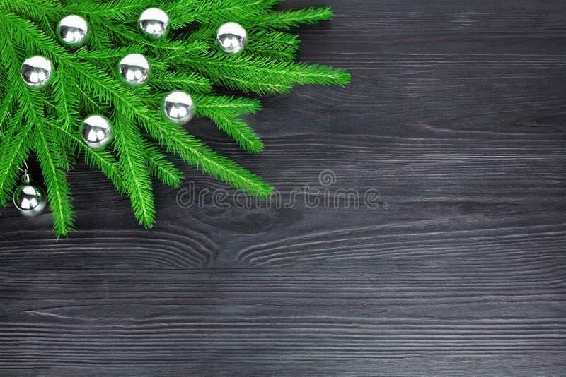 Weihnachtsfestliche Eckgrenze, dekorativer Rahmen des neuen Jahres, silberne Glaskugeldekorationen auf grünen Tannenzweigen auf s lizenzfreies stockfoto