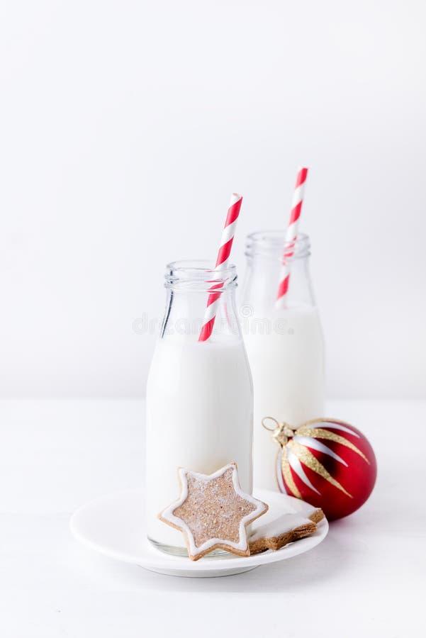 Weihnachtsfestliche Lebkuchen-Plätzchen und Flasche mit Milch und Nahrungsmittelkonzept Straw White Wooden Background Verticals H stockfoto