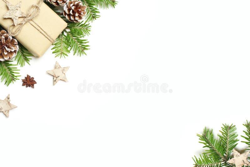 Weihnachtsfestliches angeredetes Archivbild Blumenrahmenzusammensetzung mit der Geschenkbox, Kiefernkegeln, Tannenbaumasten, hölz lizenzfreie stockbilder
